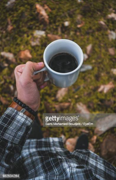 Low Section Of Man Having Black Coffee While Standing On Field