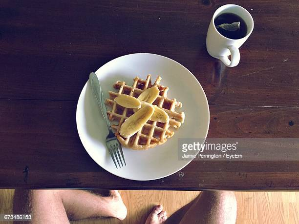 Low Section Of Man Having Breakfast On Table At Home