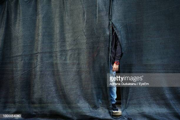 Low Section Of Man Hiding Behind Curtain
