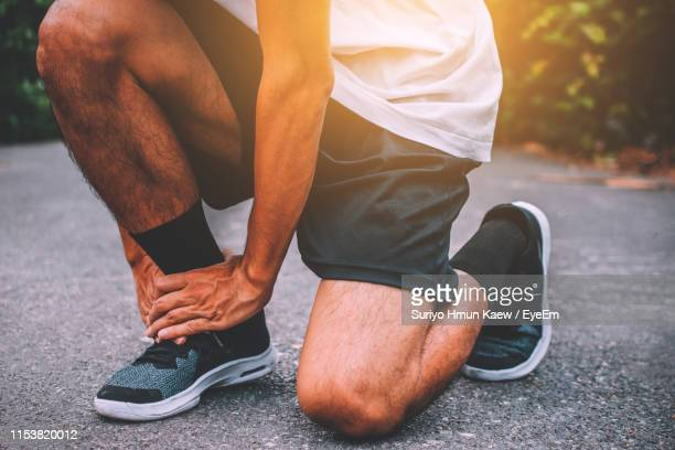 low section of man holding aching ankle while kneeling outdoors - ankle stock pictures, royalty-free photos & images