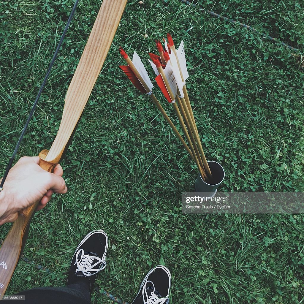Low Section Of Man Holding Bow While Standing By Arrows On Field : Stock Photo