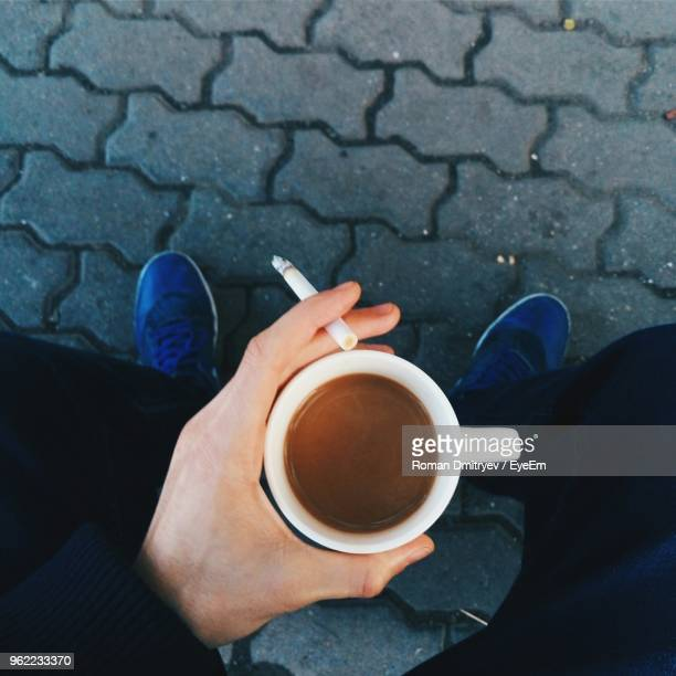 low section of man holding cigarette and coffee cup - zigarette stock-fotos und bilder