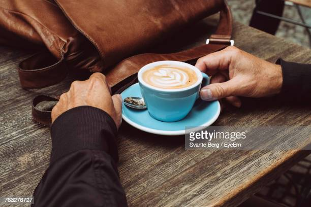 Low Section Of Man Holding Coffee Cup On Table