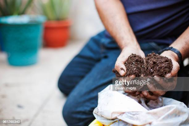 low section of man holding compost while gardening in balcony - humus photos et images de collection