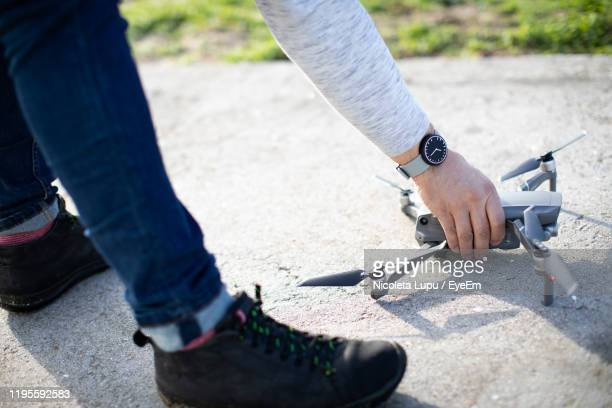 low section of man holding drone on road in city - low section stock pictures, royalty-free photos & images