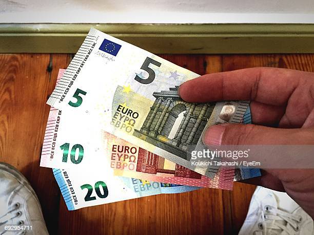 low section of man holding european union currency at home - five euro banknote stock photos and pictures