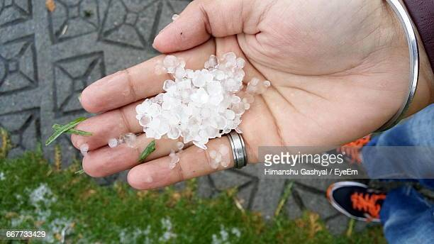Low Section Of Man Holding Hailstones On Footpath