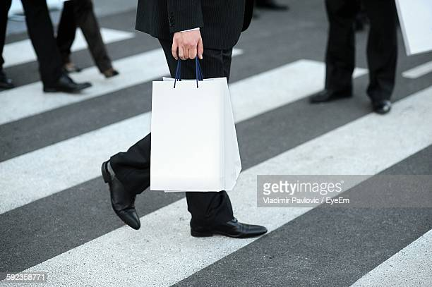 Low Section Of Man Holding Paper Bag While Walking On Zebra Crossing