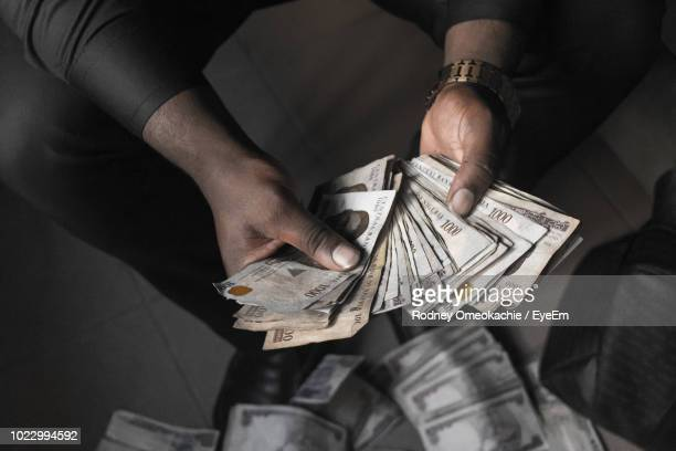 low section of man holding paper currencies - abuja stock pictures, royalty-free photos & images