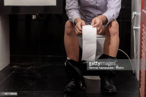 low section of man holding toilet paper while defecating in bathroom - defecare foto e immagini stock