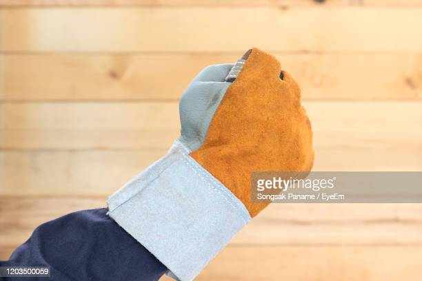 low section of man holding umbrella - leather glove stock pictures, royalty-free photos & images