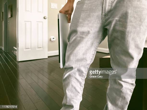 low section of man in baggy jeans holding laptop - baggy pants stock photos and pictures