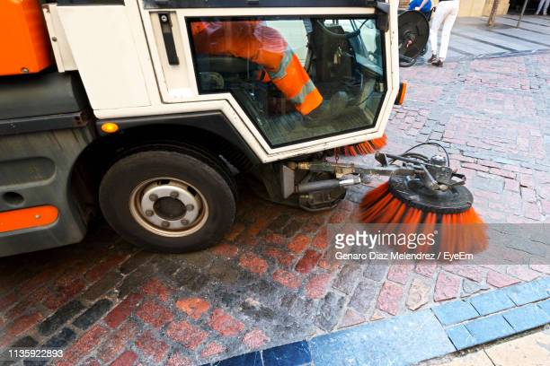 low section of man in cleaning vehicle on footpath - city cleaning stock pictures, royalty-free photos & images