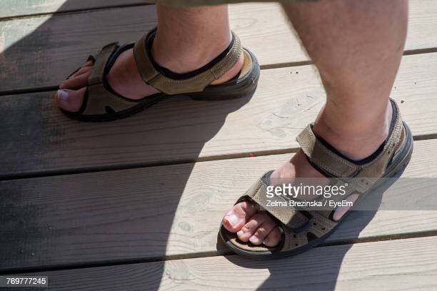 low section of man in sandals on sunny day - sandal stock pictures, royalty-free photos & images