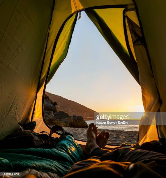 Low Section Of Man In Tent At Beach During Sunset