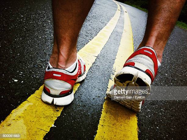 Low section of man jogging on road