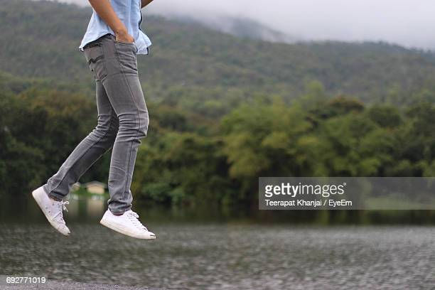 low section of man jumping by lake against tree mountains - ポケットに手を入れている ストックフォトと画像