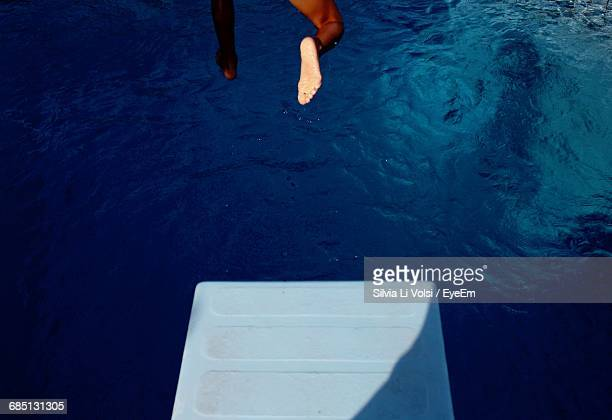 low section of man jumping into swimming pool - diving board stock pictures, royalty-free photos & images