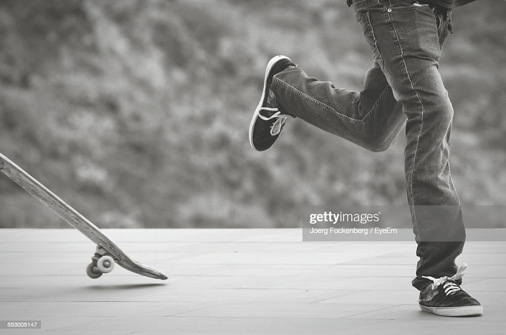Low Section Of Man Jumping Off Skateboard : Stock Photo
