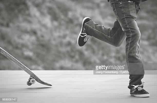 Low Section Of Man Jumping Off Skateboard