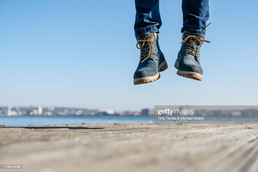 Low section of man jumping on pier on sunny day in Germany. : Stock Photo