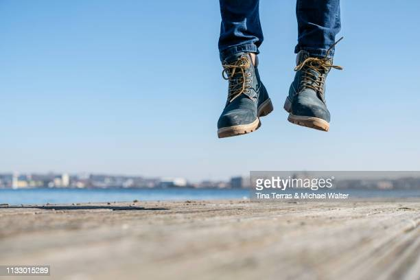 low section of man jumping on pier on sunny day in germany. - blue shoe stock pictures, royalty-free photos & images