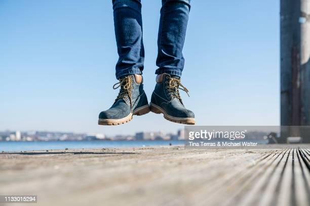 low section of man jumping on pier on sunny day in germany. - sonnig imagens e fotografias de stock