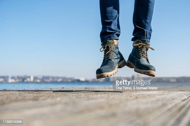 low section of man jumping on pier on sunny day in germany. - vitalität stock pictures, royalty-free photos & images