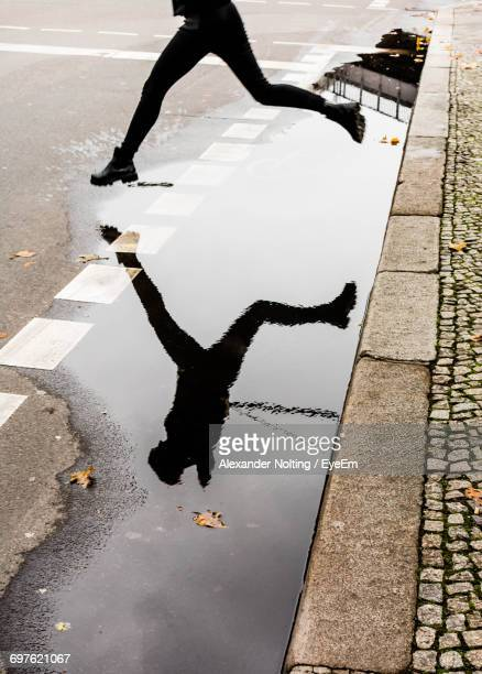 low section of man jumping over puddle on street during rainy season - charco fotografías e imágenes de stock