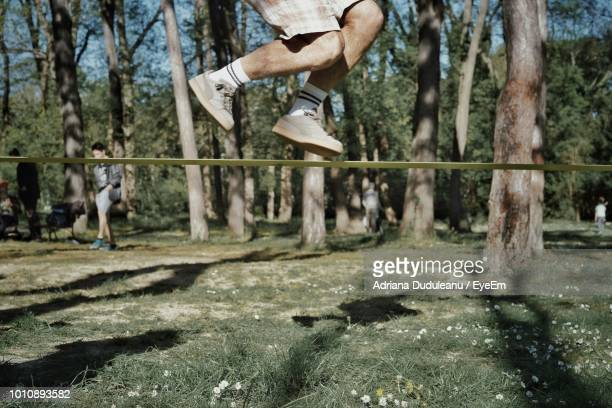 Low Section Of Man Jumping Over Rope In Forest