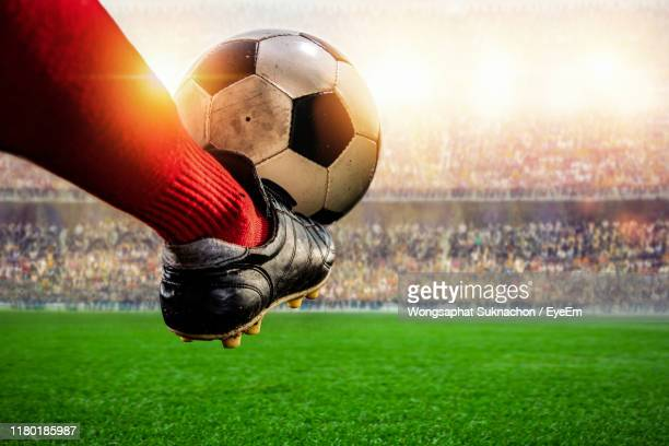 low section of man kicking ball on grass - kicking stock pictures, royalty-free photos & images