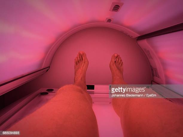 Low Section Of Man Lying Down On Tanning Bed