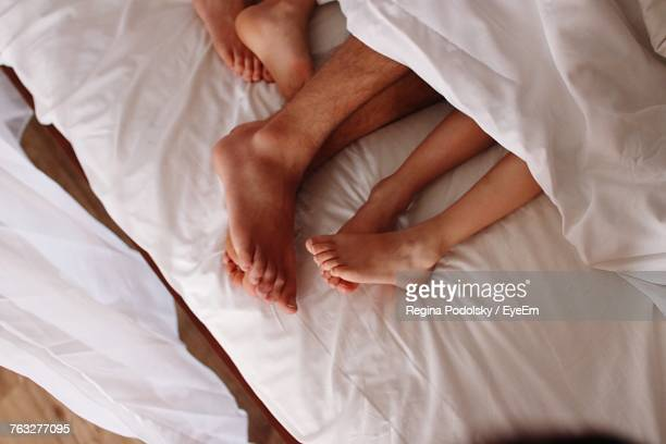 Low Section Of Man Lying In Bed