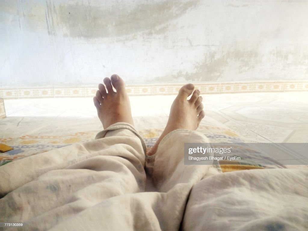 Low Section Of Man Lying On Bed : Photo