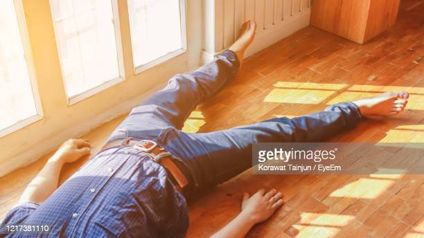 low section of man lying on floor at home - unconscious stock pictures, royalty-free photos & images