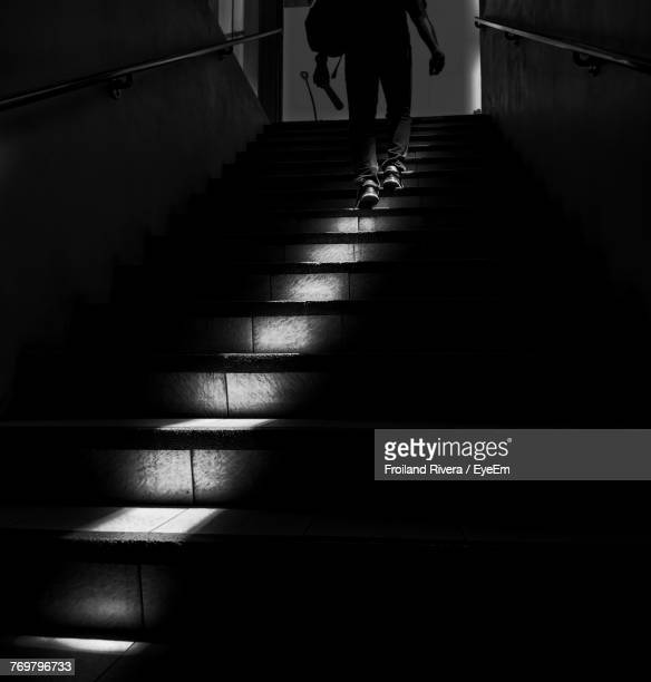 Low Section Of Man Moving Up On Steps In Darkroom