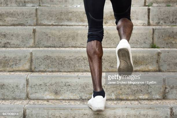 low section of man moving up on steps - stairs stock photos and pictures