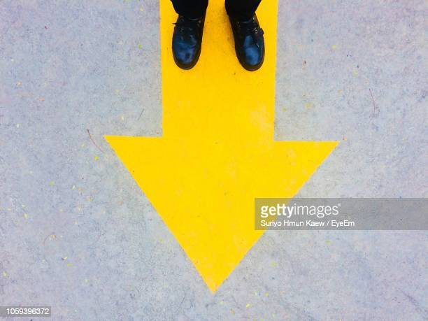 low section of man on arrow symbol - thoroughfare stock pictures, royalty-free photos & images
