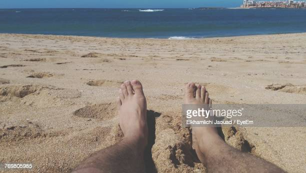 Low Section Of Man On Sand At Beach