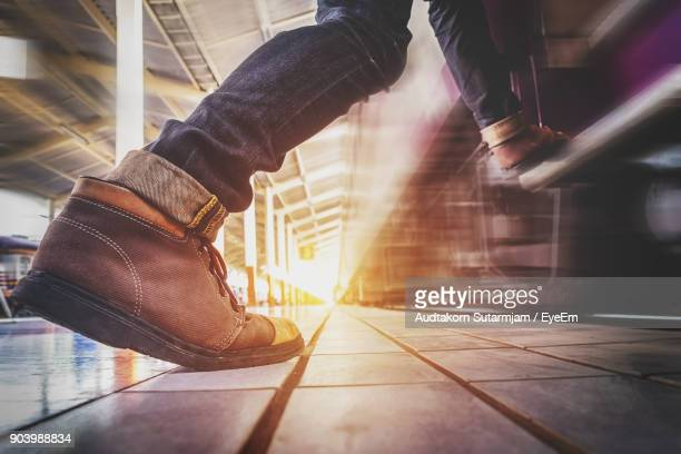 Low Section Of Man On Stepping On Train At Railroad Station Platform