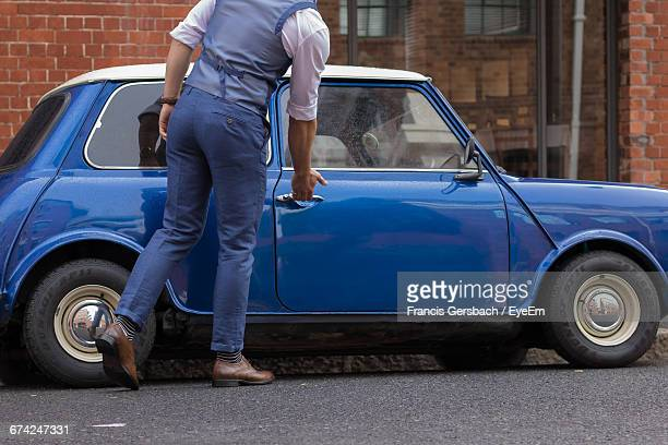 Low Section Of Man Opening Car Door On Street