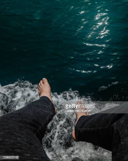 low section of man over sea - arab feet photos et images de collection