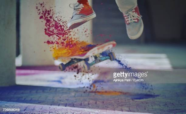 Low Section Of Man Performing Stunt While Powder Paint Splashing From Skateboard