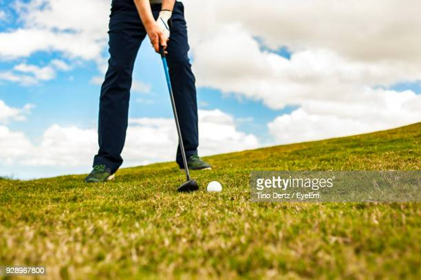 Low Section Of Man Playing Golf On Course Against Sky
