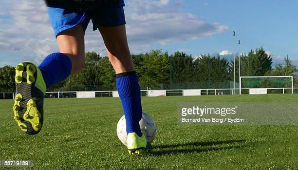 Low Section Of Man Playing Soccer At Field Against Sky