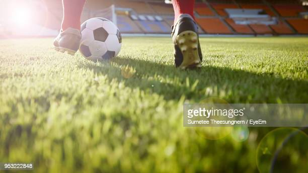 low section of man playing soccer at stadium on sunny day - soccer stock pictures, royalty-free photos & images