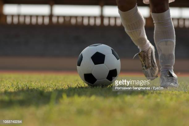 low section of man playing soccer on grassy field - low section stock pictures, royalty-free photos & images