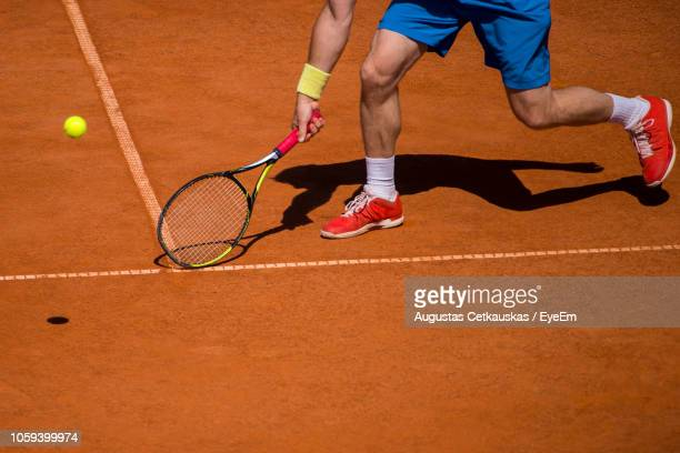 low section of man playing tennis on court - tennis player stock pictures, royalty-free photos & images