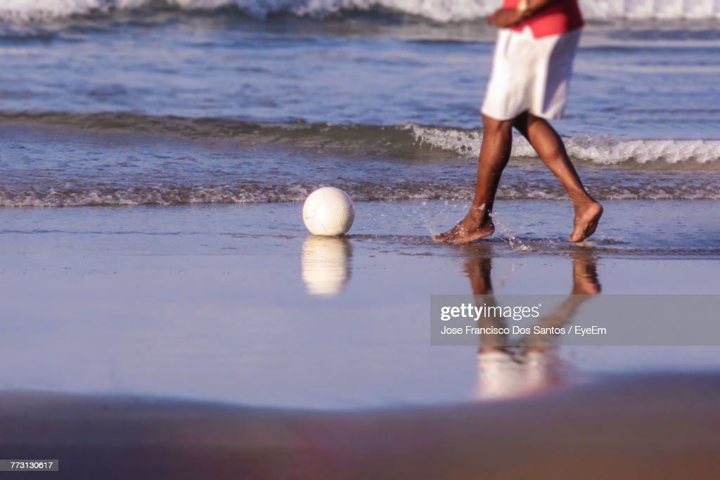 Low Section Of Man Playing With Ball At Beach : Photo