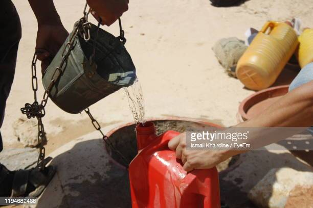 low section of man pouring water from bucket in container at well - ismail khairdine - fotografias e filmes do acervo